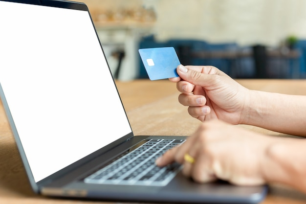 Carta di credito della tenuta della mano dell'uomo d'affari e computer portatile usando sulla tavola di legno.