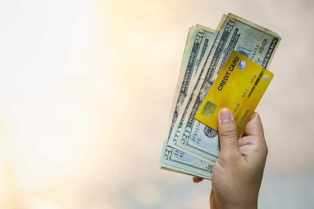 Carta di credito della tenuta della mano della donna e banconota da 20 dollari americani con lo spazio della copia