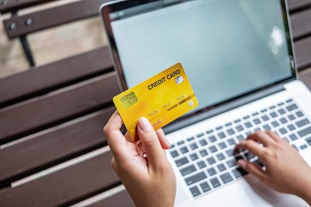 Carta di credito della tenuta della mano della donna e computer portatile usando, concetto online di acquisto