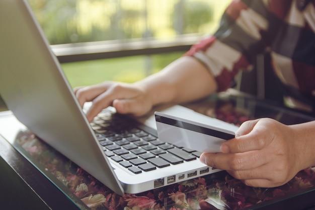 Carta di credito della tenuta della mano della donna ed uso del computer portatile che effettua pagamento online online