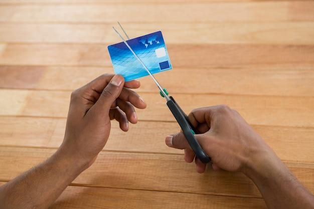 Carta di credito di taglio dell'uomo d'affari con le forbici
