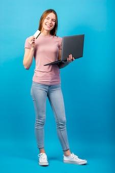 Carta di credito e computer portatile della tenuta della donna della foto a figura intera