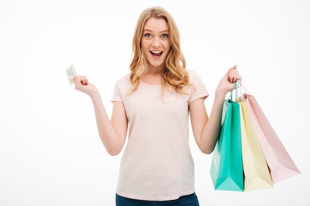 Carta di credito e sacchetti della spesa allegri della tenuta della giovane donna.