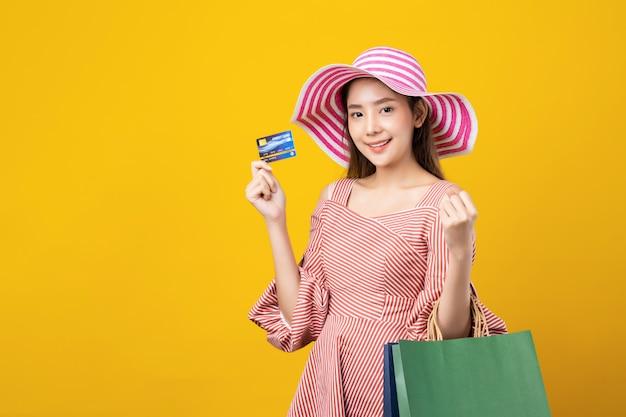 Carta di credito e sacchetti della spesa asiatici abbastanza svegli della tenuta della giovane donna con il fronte di smiley che sta nello studio.