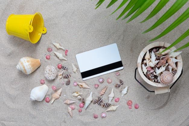 Carta di credito ed elementi della spiaggia sulla sabbia