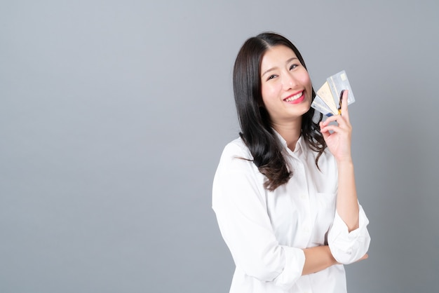 Carta di credito presente sorridente felice della giovane donna asiatica in mano su gray