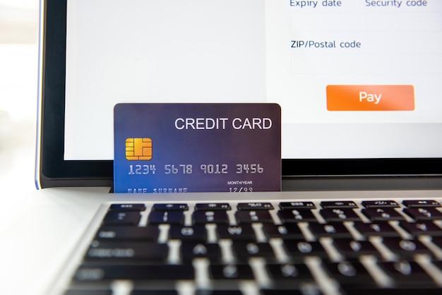 Carta di credito sul computer portatile che rappresenta il pagamento online