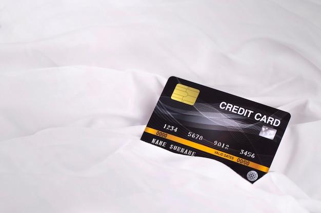 Carta di credito sul fondo di struttura del tessuto del panno bianco