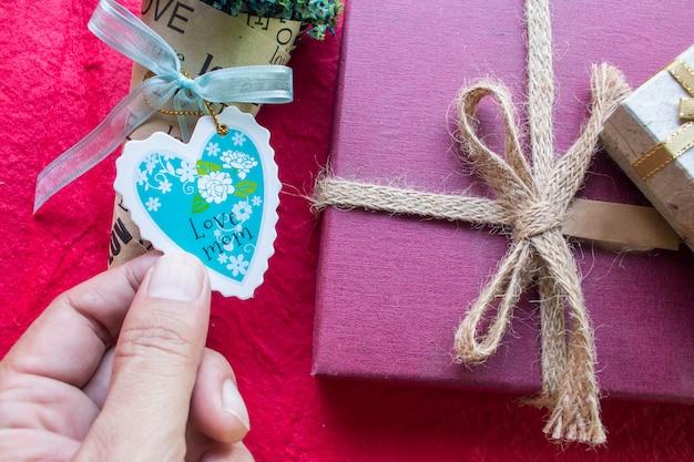 Carta di giorno di madri a forma di cuore con la mano maschile sul contenitore di regalo