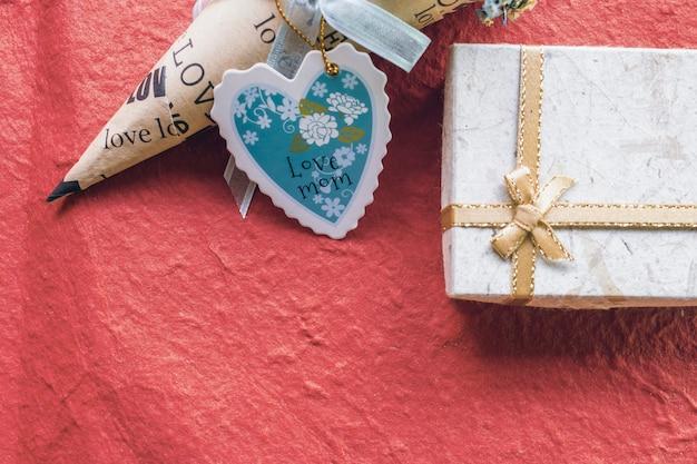 Carta di giorno di madri a forma di cuore con scatola regalo su sfondo rosso