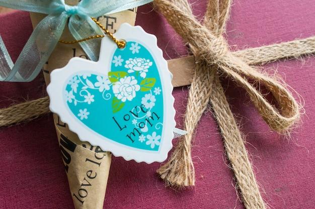 Carta di giorno di madri a forma di cuore sulla confezione regalo
