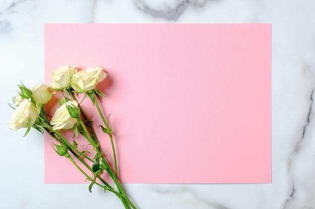 Carta di invito a nozze. fiori di rosa e carta di carta rosa in bianco su fondo di marmo. concetto di matrimonio.