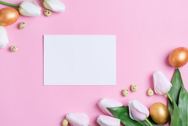 Carta di invito di buona pasqua da uova dipinte artigianali, foglio di carta e fiori freschi.