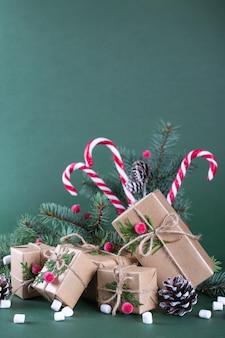 Carta di natale o capodanno. coppa con abeti, bastoncini di zucchero. confezioni regalo in carta artigianale beige vintage e decorazioni naturali.