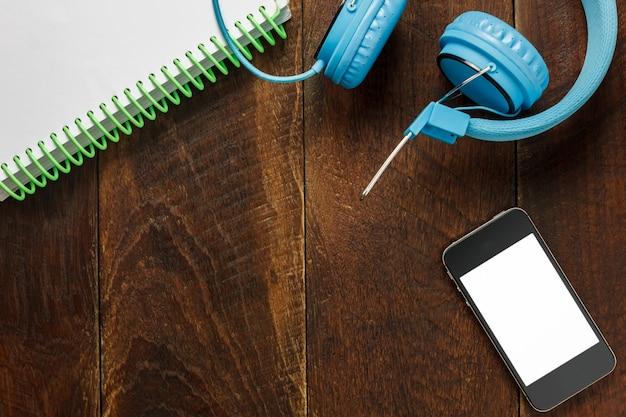Carta di nota superiore vista, cuffie, smartphone, matita, sullo sfondo della scrivania di legno di ufficio.