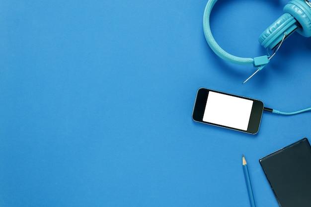 Carta di nota vista superiore, cuffie, smartphone, matita, su sfondo blu.