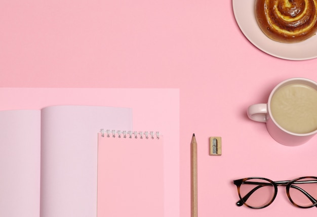 Carta di note rosa, matita di legno, temperamatite, tazza di caffè, torta su sfondo rosa
