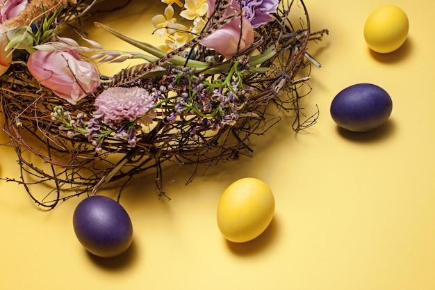 Carta di pasqua. uova di pasqua dipinte in nido su giallo