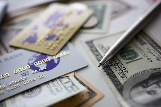 Carta di plastica bancaria e penna d'argento che giace su una grande quantità di denaro degli stati uniti