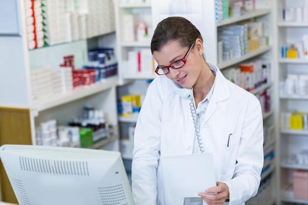 Carta di prescrizione della tenuta del farmacista mentre parlando sul telefono