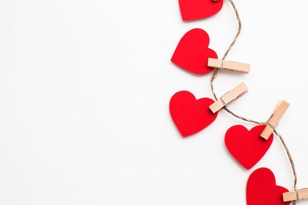 Carta di san valentino. bianco con cuori rossi su mollette.
