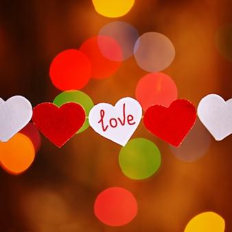 Carta di san valentino con cuori rossi e bianchi e parole d'amore su luci colorate bokeh