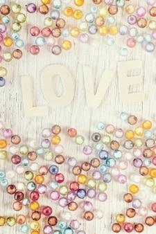 Carta di san valentino con testo amore e mucchio di perline su legno, dolce colore pastello tonica.