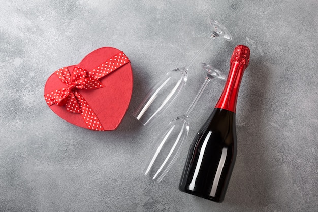 Carta di san valentino con una bottiglia di champagne, occhiali con una scatola di cioccolatini a forma di cuore.