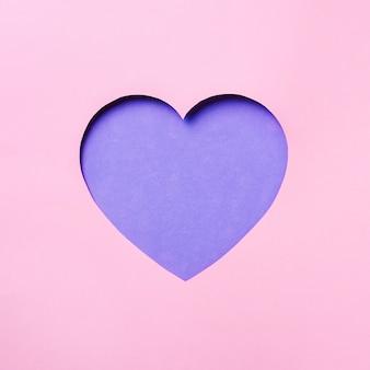 Carta di san valentino. cuore cutted in incisivo fondo di carta pastello.