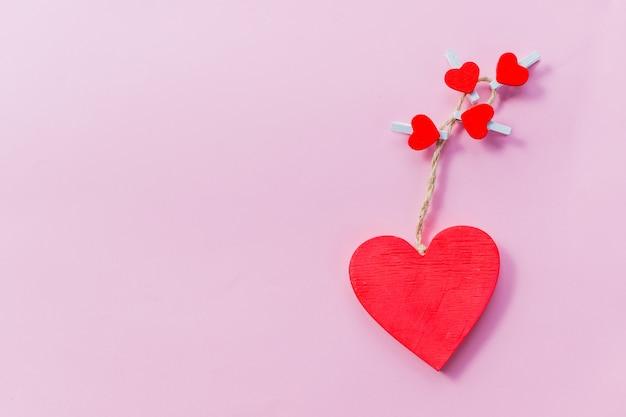 Carta di san valentino. cuori rossi di legno isolati sul concetto rosa di giorno di s. valentino di background.happy. cartolina festiva. concetto di amore per la festa della mamma e il giorno di san valentino. copi lo spazio
