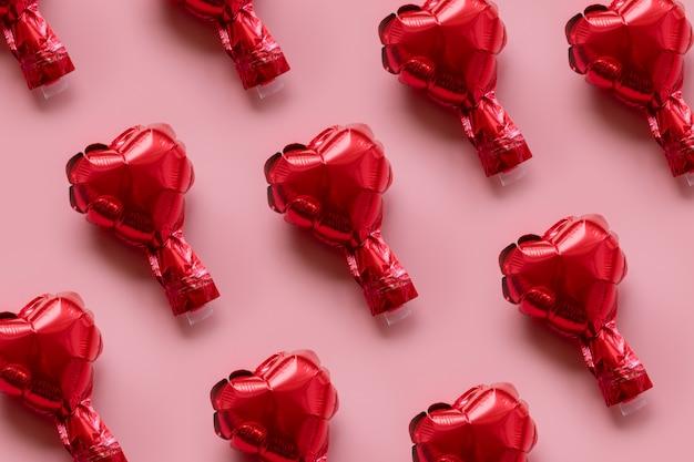 Carta di san valentino: modello di palloncini stagnola rosso su sfondo rosa