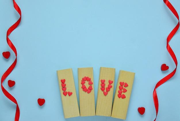 Carta di san valentino. sfondo di san valentino. cuore rosso, nastro rosso su sfondo blu pastello.