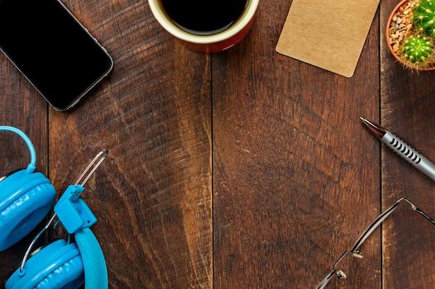 Carta di tag della vista superiore, cuffie, smartphone, penna, caffè, cactus, occhiali da vista sullo sfondo della scrivania.