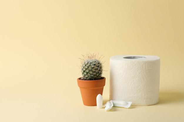 Carta igienica, candele e cactus su beige. emorroidi