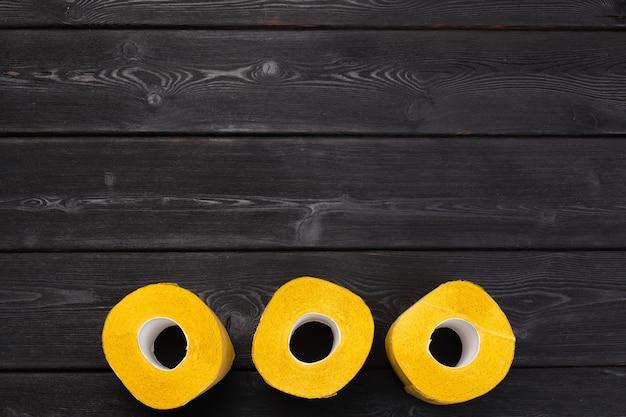 Carta igienica gialla sulla vista di legno nera del piano d'appoggio