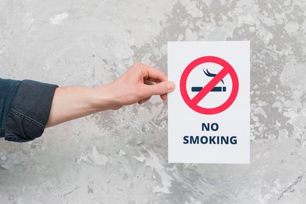 Carta maschio della tenuta della mano con il segno e testo non fumatori sopra la parete stagionata