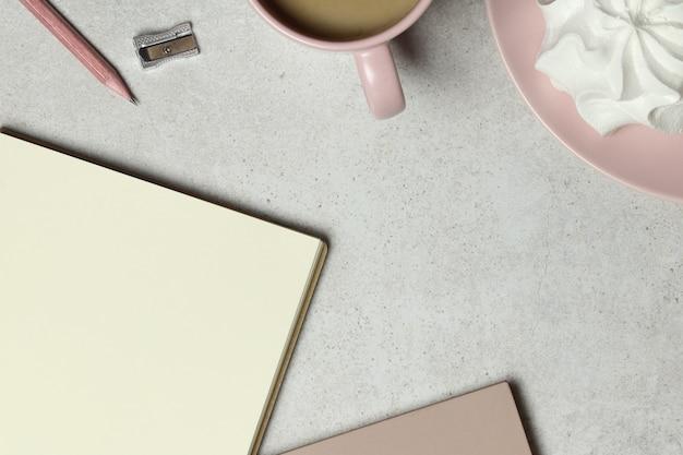 Carta notebook, matita, temperino, tazza di caffè, marshmallow su sfondo granato