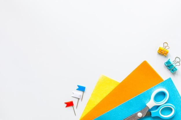 Carta origami multicolore e forbici su sfondo bianco con spazio di copia.
