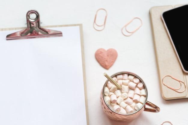 Carta, penna, telefono e cacao su un'area di lavoro sulla scrivania