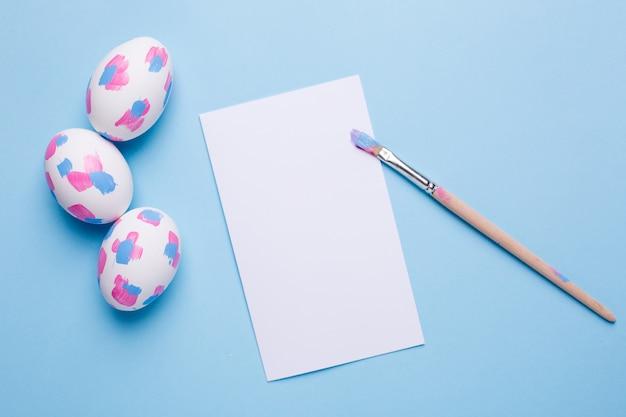 Carta, pennello e uova di pasqua con pennellate di acquerello