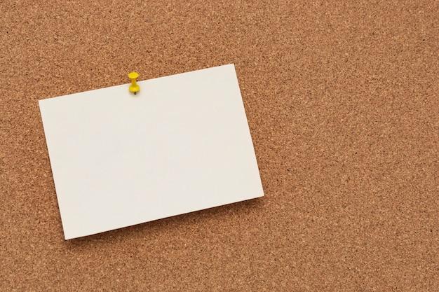 Carta per appunti con puntina sul bordo di sughero
