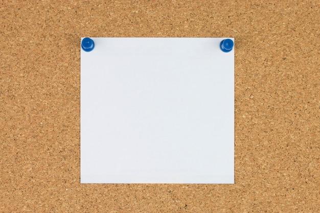 Carta per appunti con puntine da disegno sul pannello di sughero