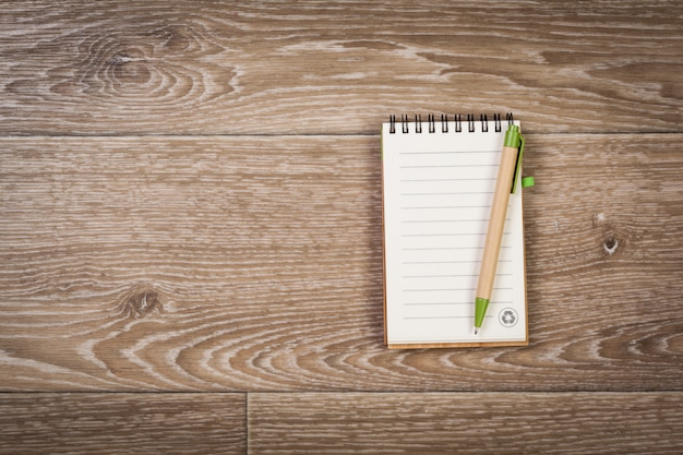 Carta per appunti in bianco con la penna su fondo di legno