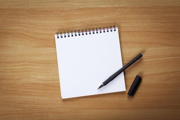 Carta per appunti in bianco con la penna sulla tavola di legno