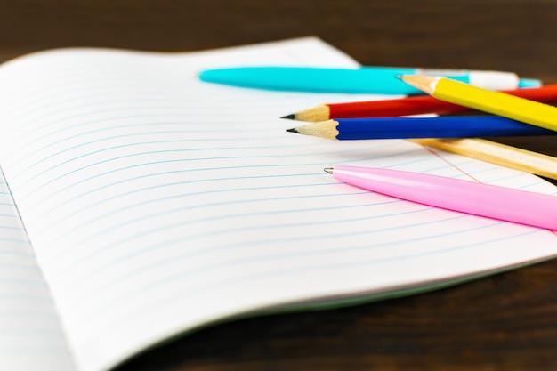 Carta per appunti in bianco con penne e matite