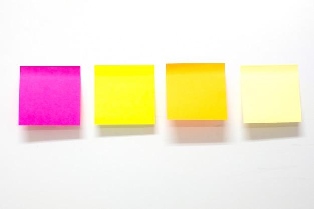 Carta per appunti in bianco del bastone o post-it su fondo bianco. promemoria e concetto di business