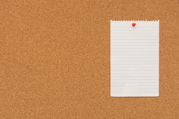 Carta per appunti spogliata con puntina sul bordo di sughero
