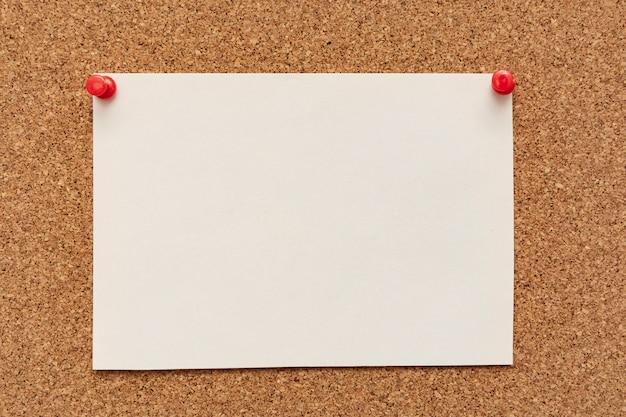 Carta per appunti spogliata con puntine da disegno sul bordo di sughero
