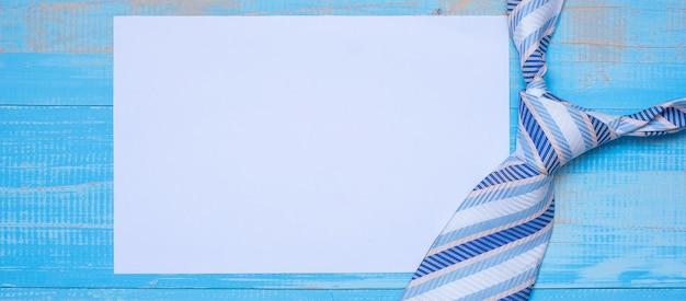 Carta per appunti vuota con cravatte blu su fondo di legno