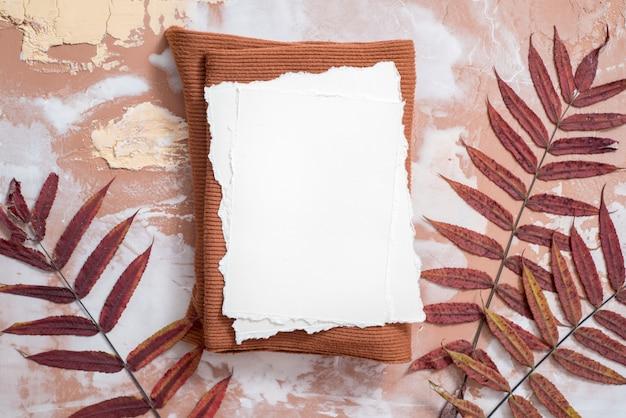 Carta per i tuoi appunti. tendenza della carta strappata. mockup di composizione autunnale. noci, foglie secche su uno sfondo marrone. calda maglia e sciarpa rosse lavorate a maglia, foglie di carta e un quaderno. carta strappata di tendenza.